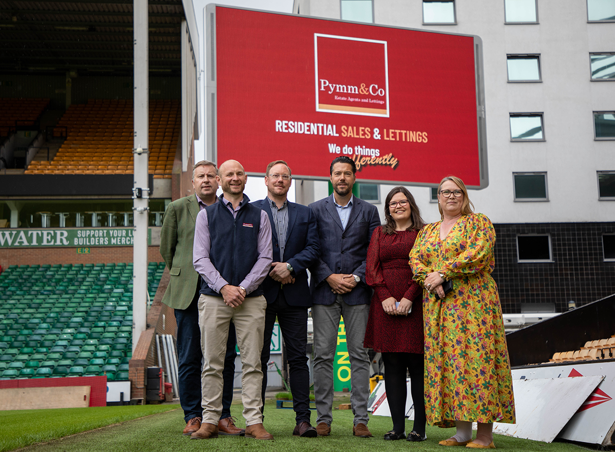 The Pymm & Co Sales and Lettings team standing in front the Pymm & Co brand takeover on the big screen at Norwich City Football Club