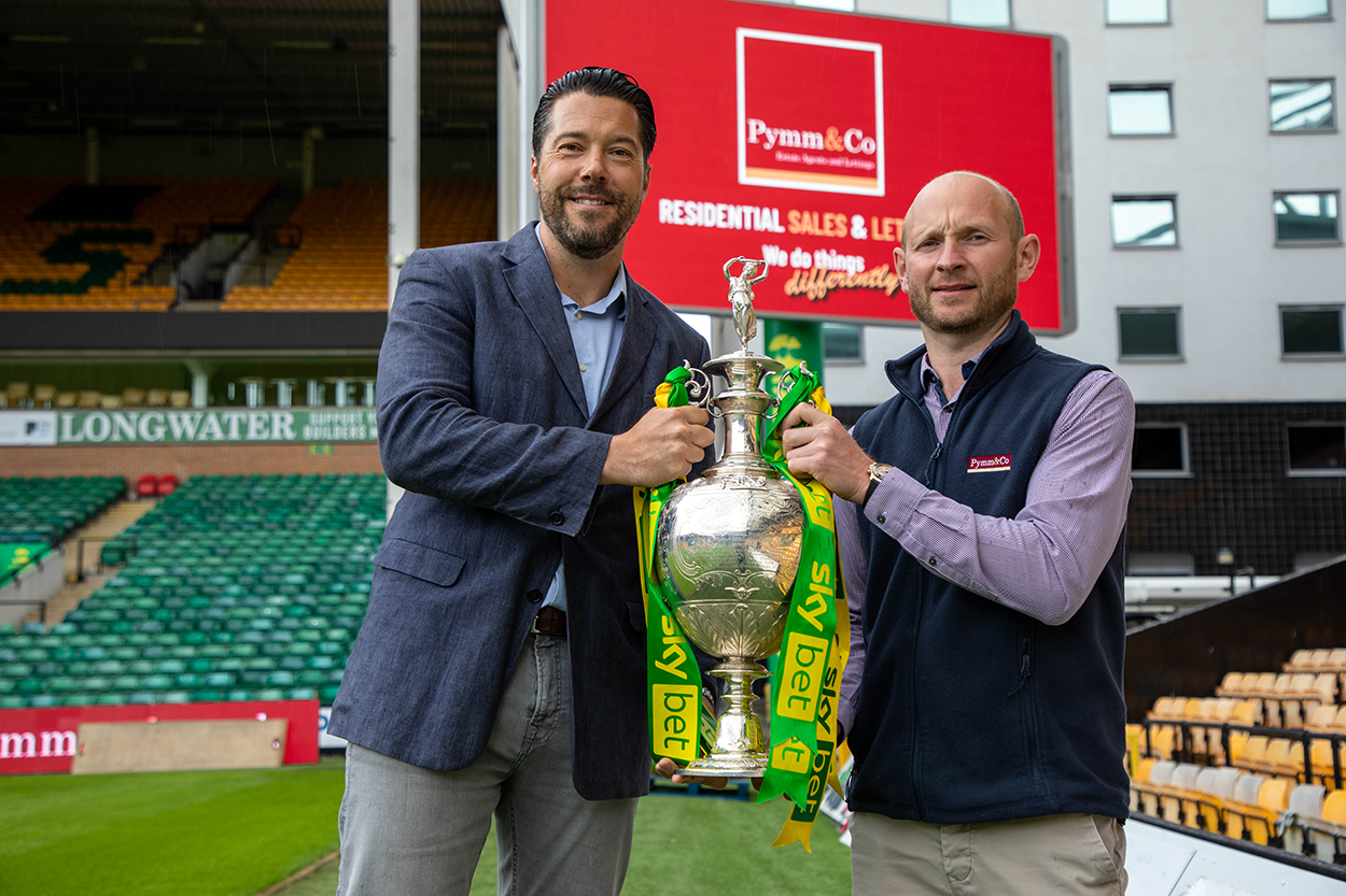 Steve Pymm and Stuart Monument standing in front of the big screen brand takeover at Norwich City Football Club.